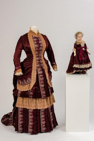 Image: Fashion doll, circa 1870s and plum coloured satin dress trimmed with ecru lace, 1880s